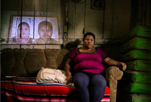 Yuni Ordoñez, widow of José Luis Pastrana. At only 26 years of age, Pastrana was the youngest of the campesinos killed on the El Tumbador plantation. Yuni is sitting in front of a projection of one of the few photographs of her husband she possesses. After she denounced the massacre, she suffered several attacks on her person, including being shot at. The day this photograph was taken, Yuni was suffering from an asthma attack but had no money to buy medicine.