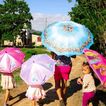 A mother with her three daughters, walking down a street in Guadalupe Carney. The area receives extremely hot tropical weather year-round.